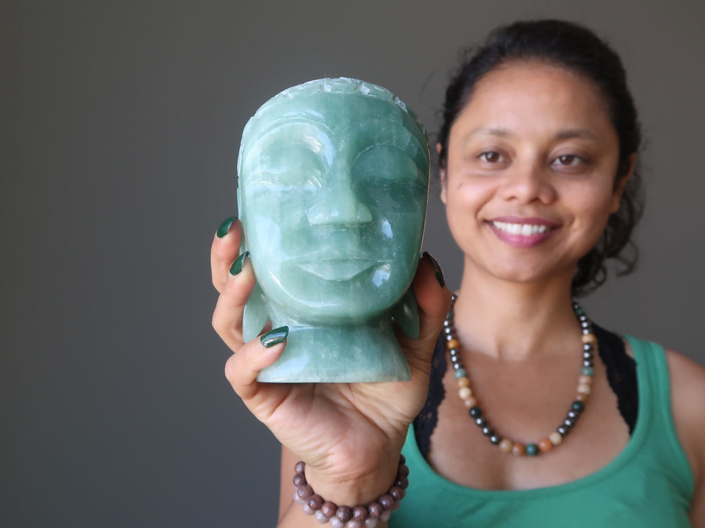 sheila of satin crystals holding a green aventurine buddha head carving
