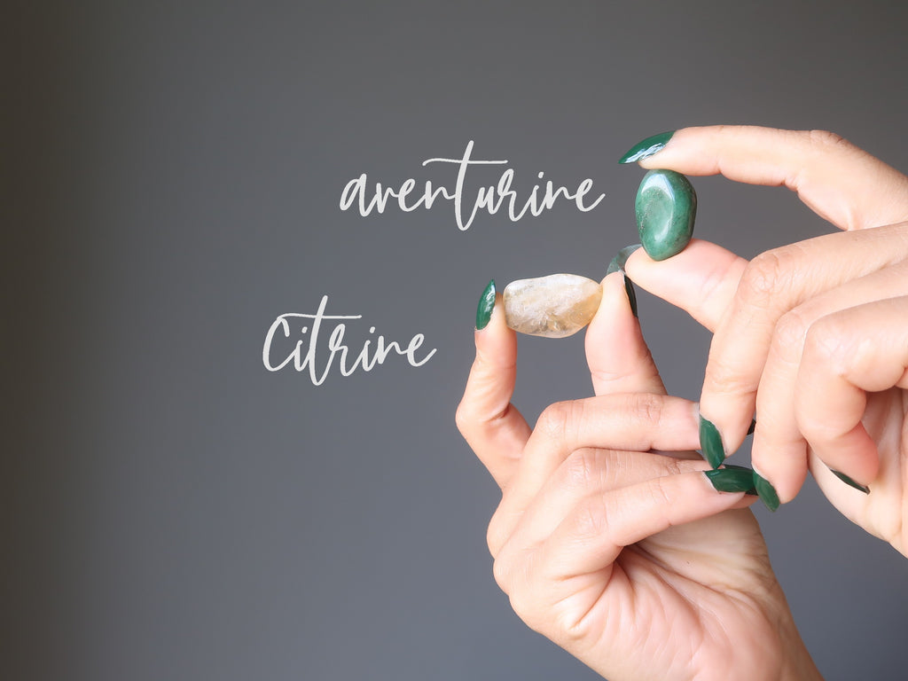 hands holding green aventurine and yellow citrine tumbled stones for abundance crystals