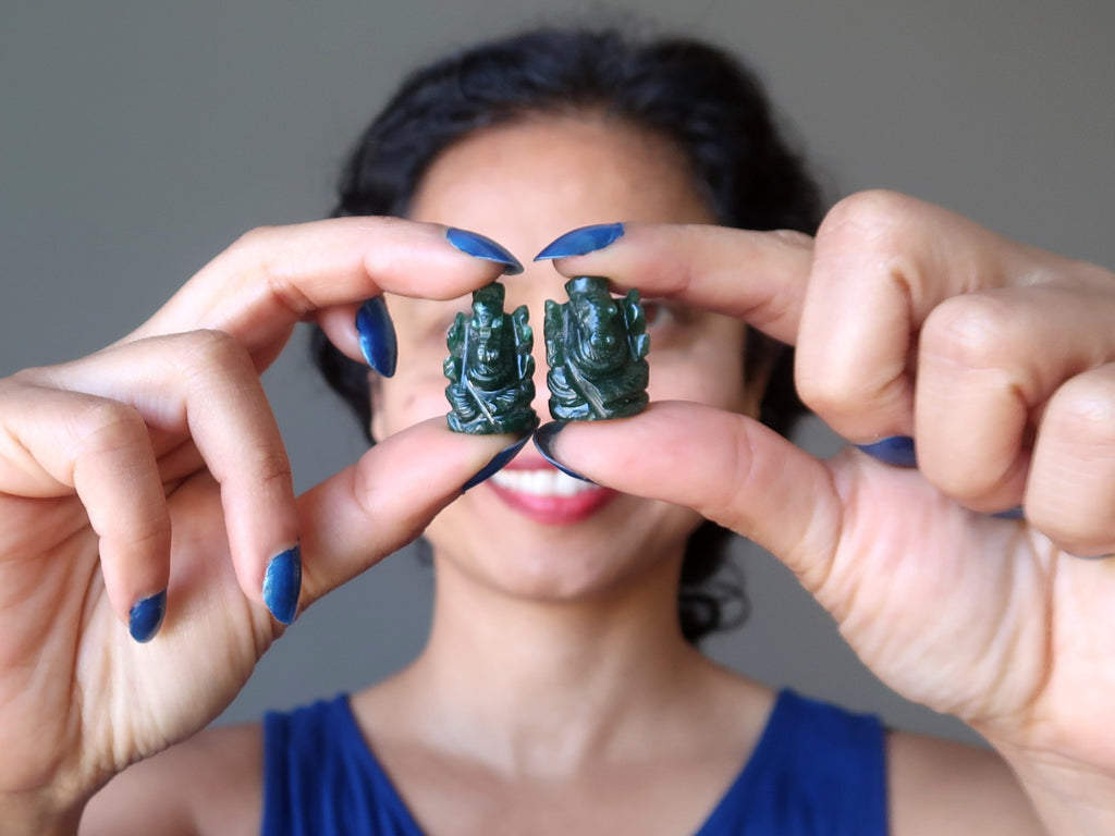 sheila of satin crystals holding up two dark green aventurine ganesh hindu elephant god figurines