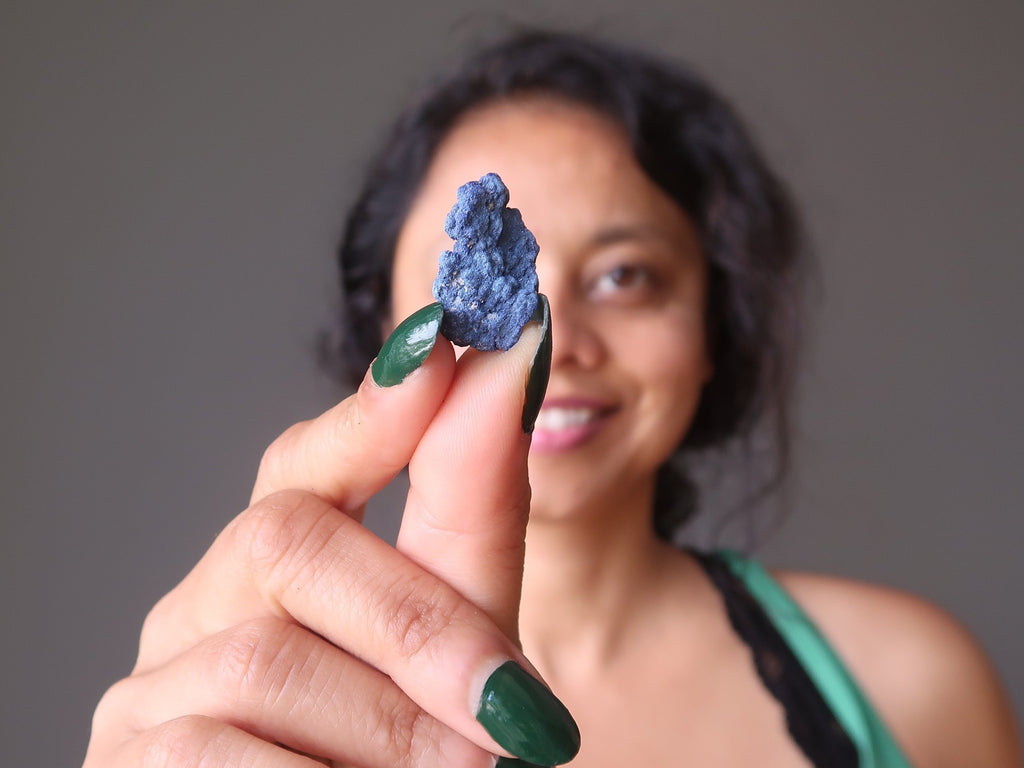sheila of satin crystals holding up a raw blue stone of azurite