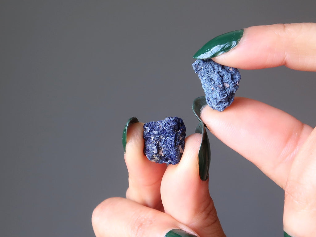 hands holding two raw nuggets of natural azurite gemstones