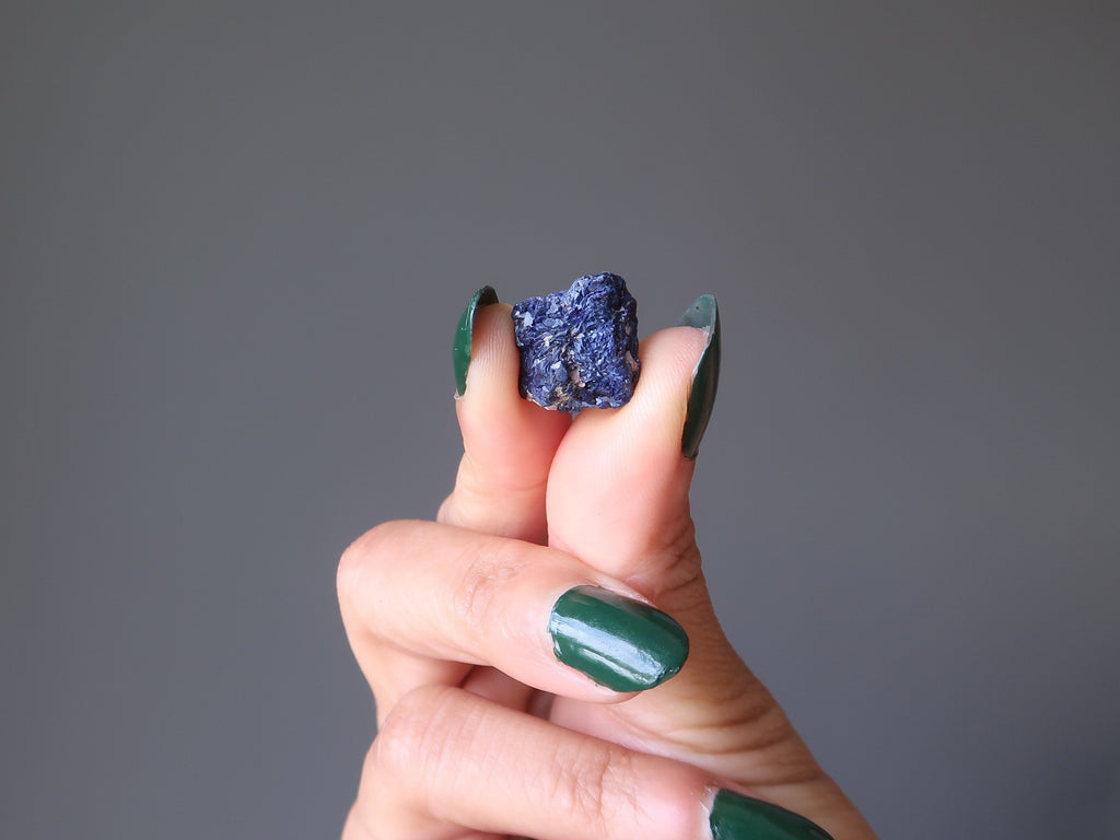 hand holding a dark blue azurite rough gemstone