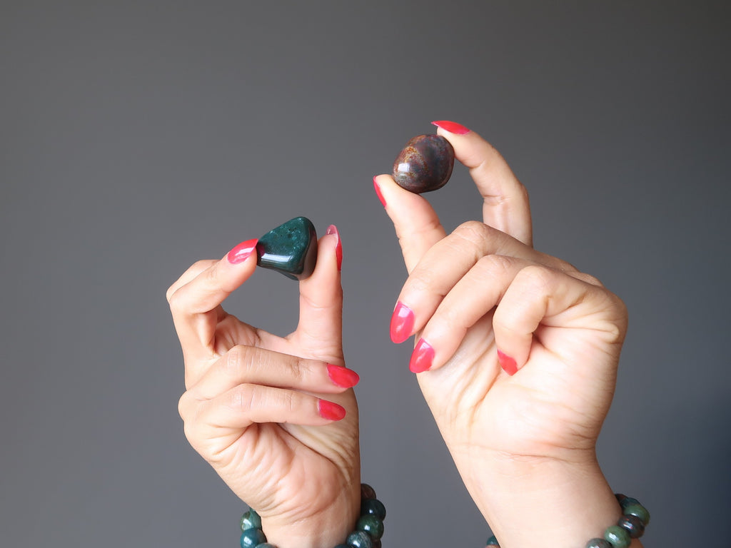 hands wearing bloodstone stretch bracelets holding up a green and red tumbled stones