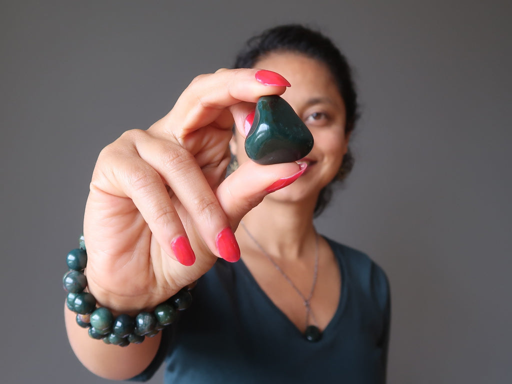 sheila of satin crystals holding up a bloodstone tumbled stone