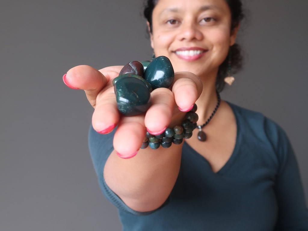sheila of satin crystals holding a hand full of green and red bloodstone tumbled stones`