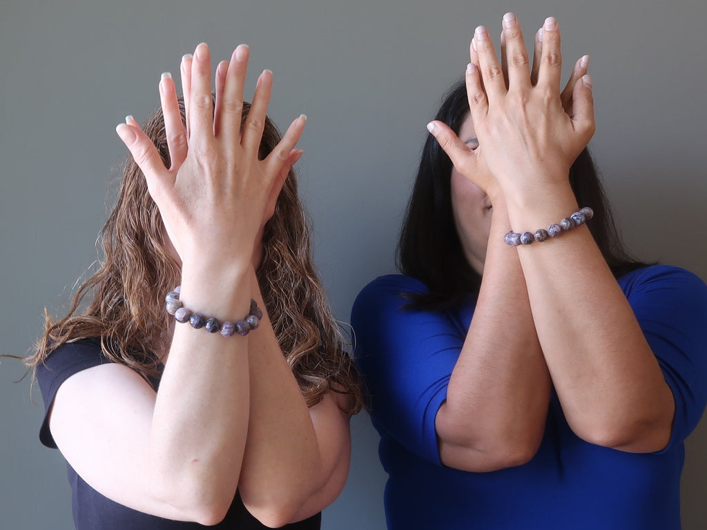 satin crystals models with their arms folded in front of their faces wearing purple charoite gemstone stretch bracelets