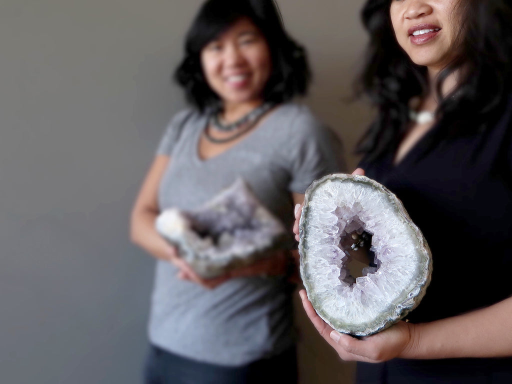 Two women holding natural raw Amethyst geodes at Satin Crystals