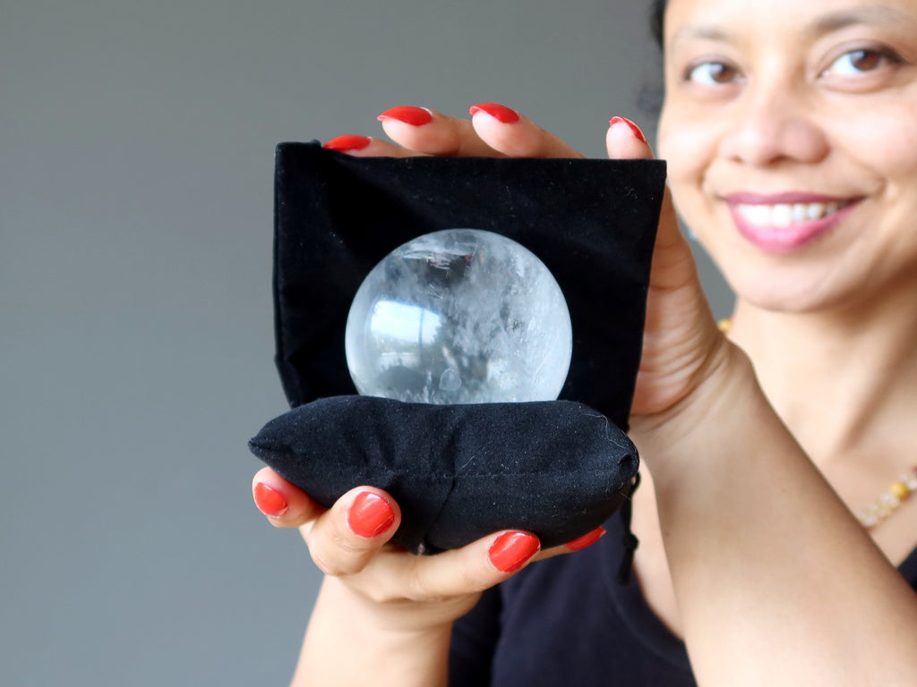 sheila of satin crystals holding a clear quartz ball on a black pillow