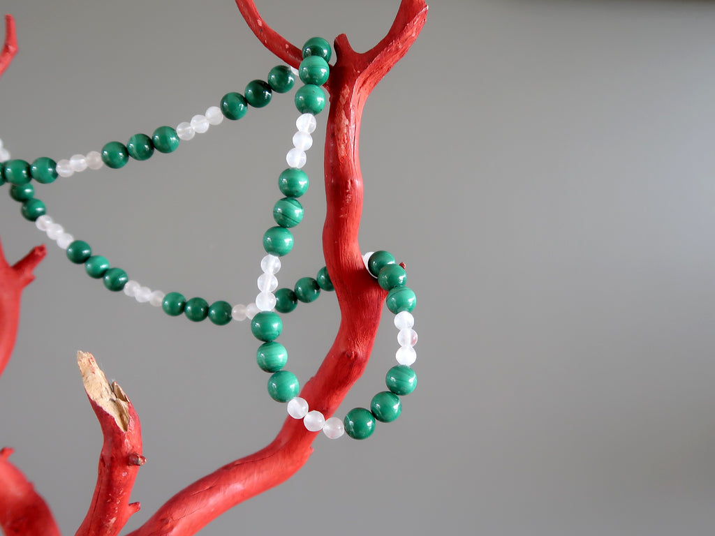 Green Malachite and white Selenite beaded necklace on a red jewelry tree branch.
