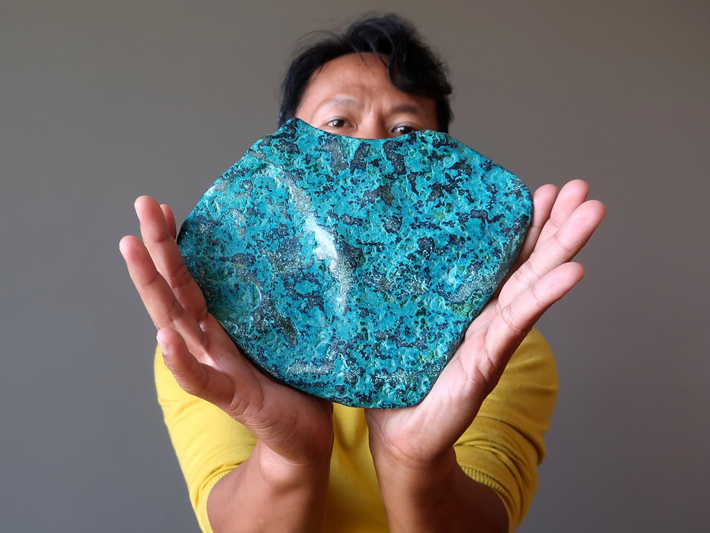 Tim of Satin Crystals holding up a raw plate of blue Chrysocolla Stone