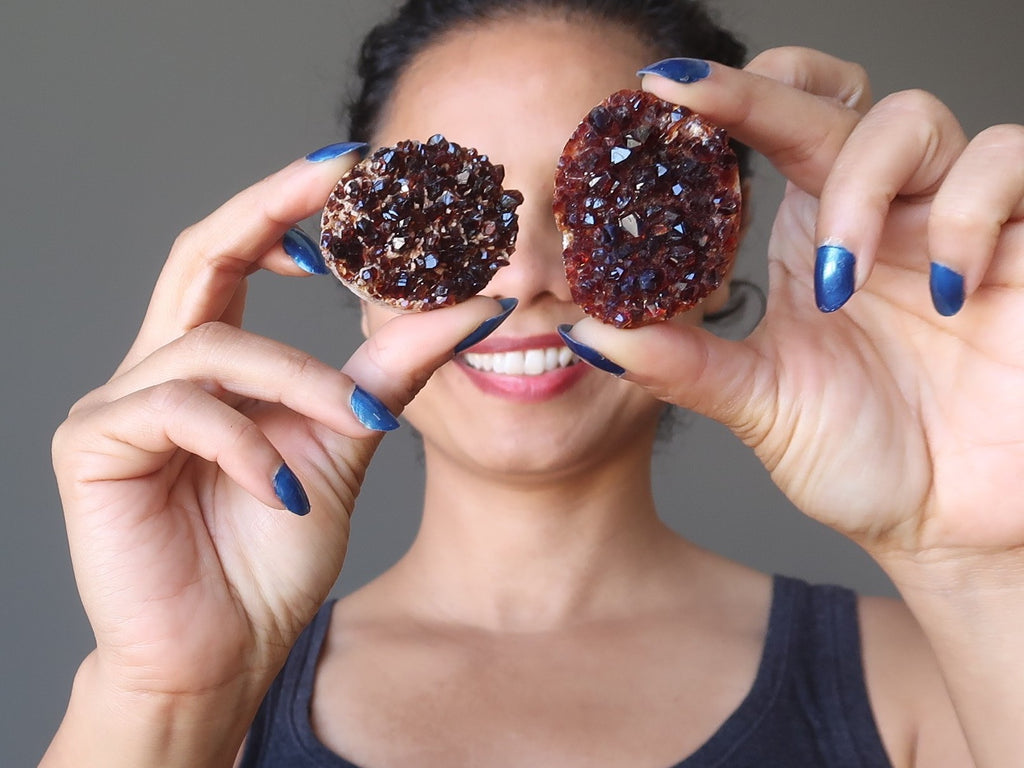 sheila of satin crystals holding up two heated citrine geode clusters