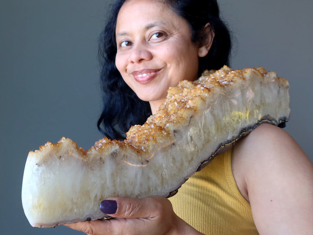 sheila of satin crystals holding a large citrine cluster geode