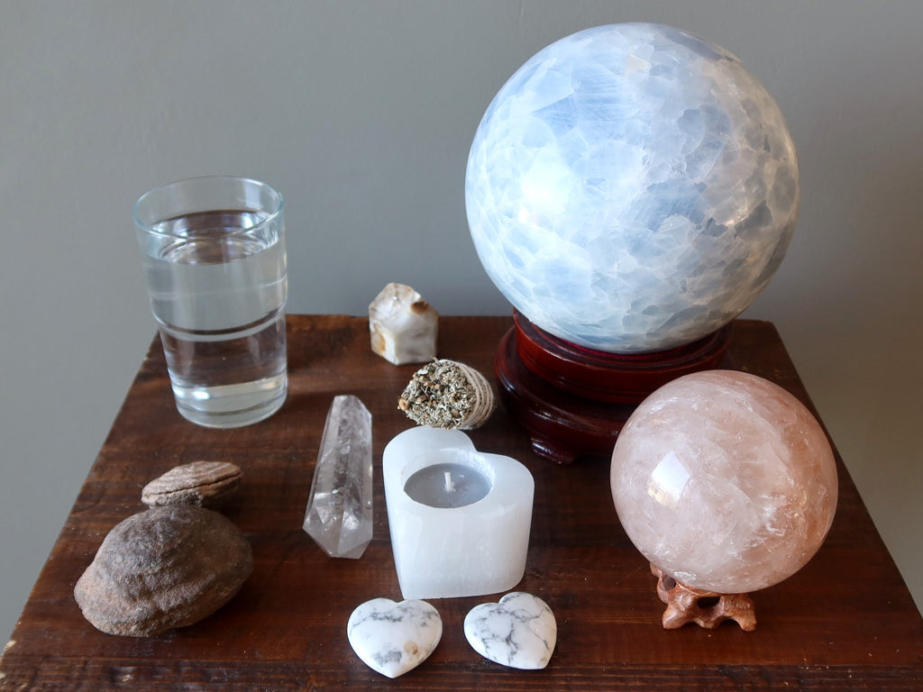 crystals, water, candle, and sage to prepare for a crystal ball gazing session