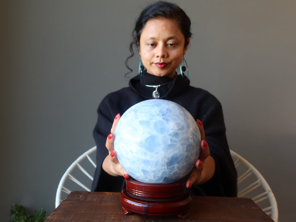 sheila of satin crystals with hands on a large blue calcite sphere