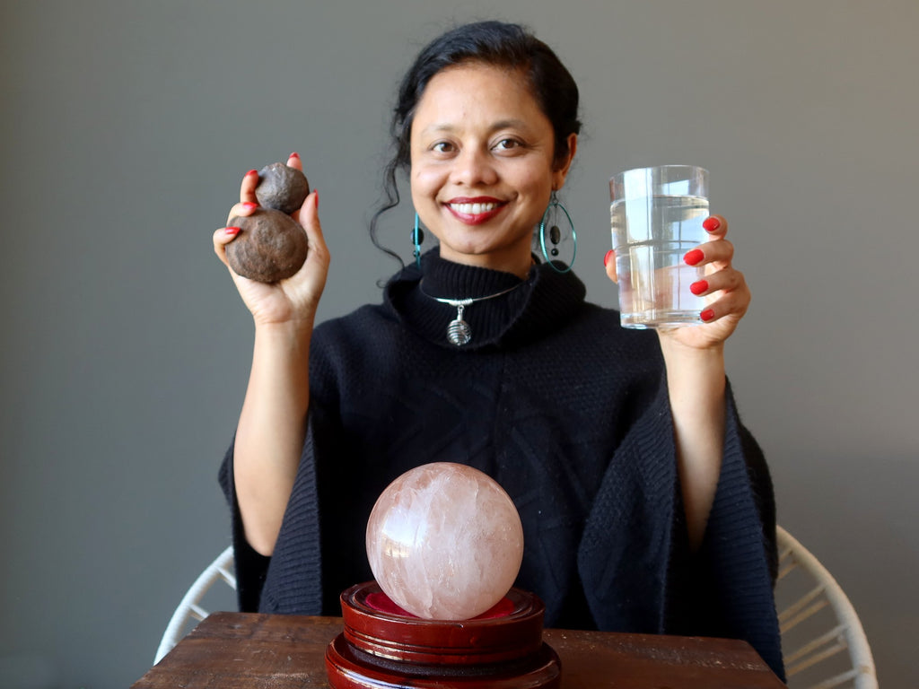 sheila of satin crystals sitting behind a red quartz sphere holding up moqui marbles and a glass of water for grounding