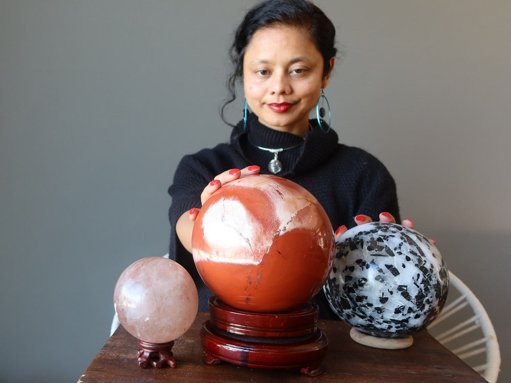 sheila of satin crystals sitting behind three large crystals balls for gazing