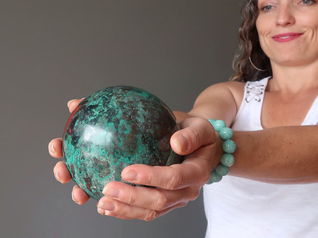 aleks of satin crystals holding out a chrysocolla crystal ball for earth healing