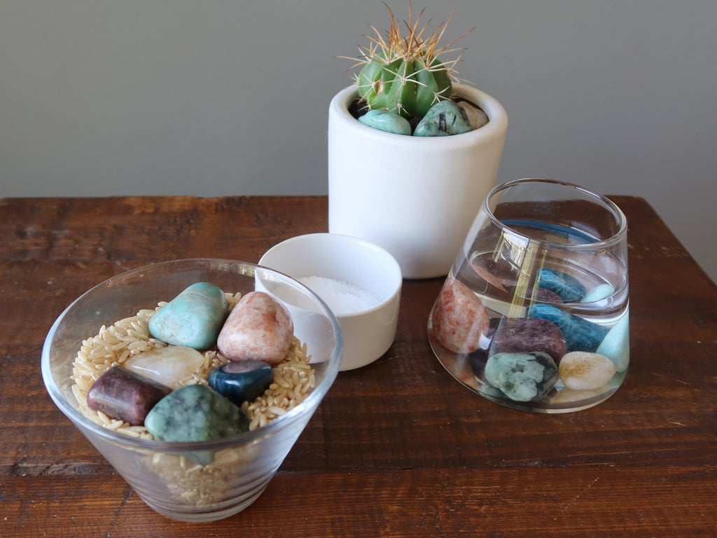 chakra crystals being cleaned in brown rice, water, potted plant and salt