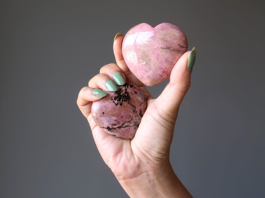 hand holding two pink and black rhodonite hearts
