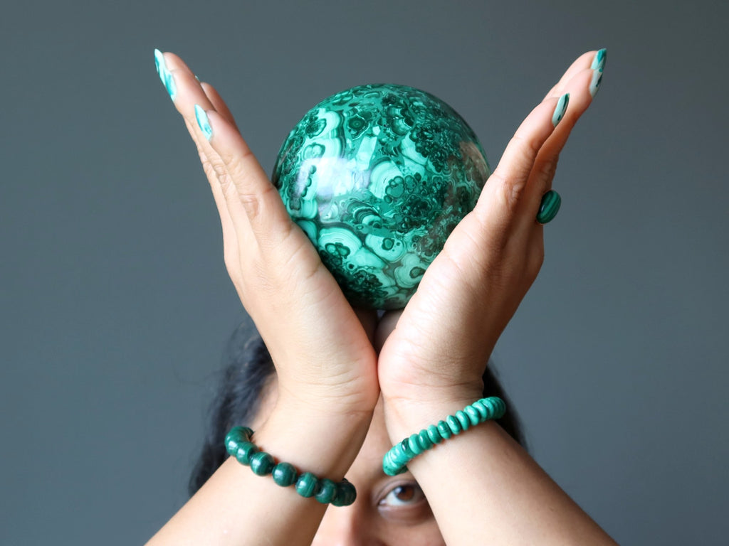 Sheila of Satin Crystals holding up a Malachite sphere at her Crown Chakra