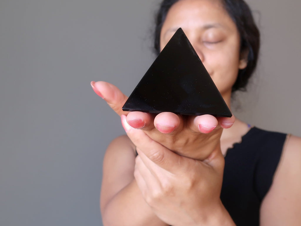 sheila of satin crystals holding a black obsidian stone pyramid