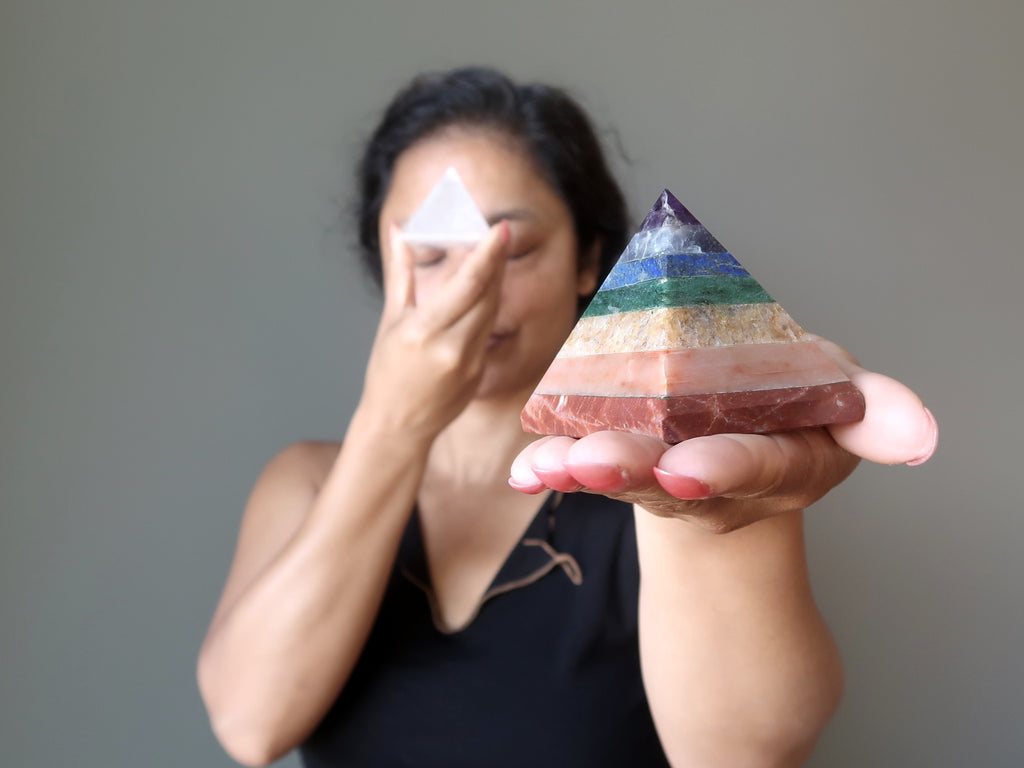 sheila of satin crystals holding up a chakra and a clear quartz stone pyramid