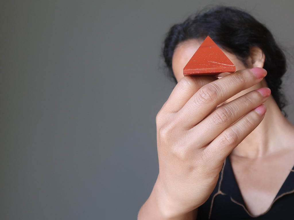sheila of satin crystals holding up a red jasper stone pyramid