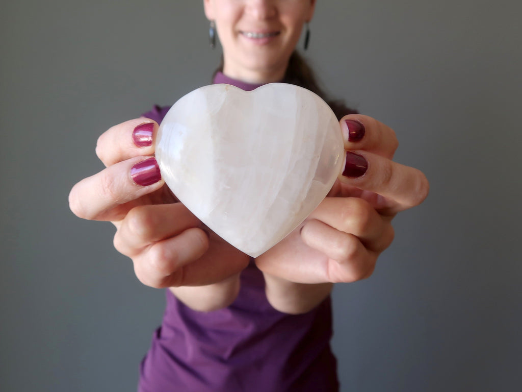 lucia of satin crystals holding a quartz heart for love and romance