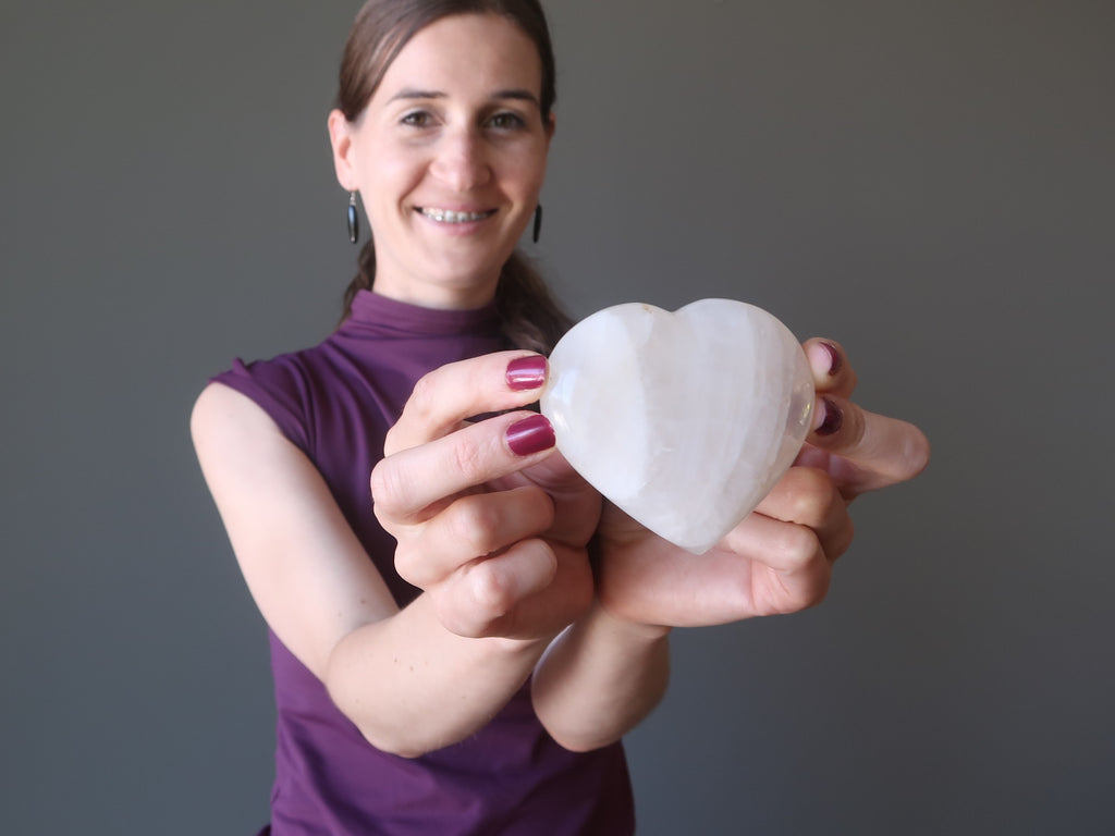 lucia of satin crystals holding up a quartz stone heart to open the chakra