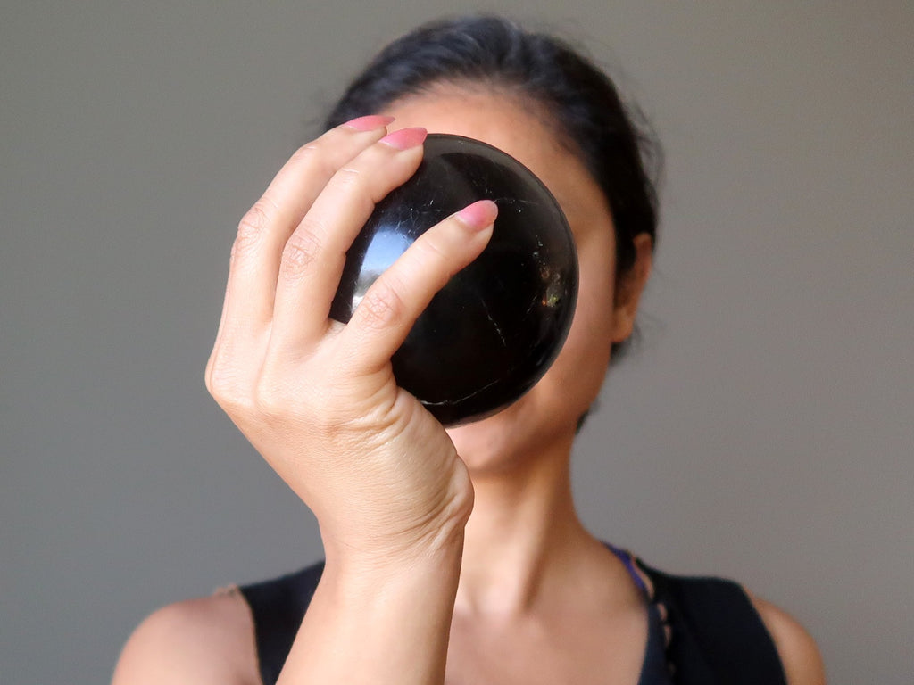 sheila from satin crystals holding up a black tourmaline stone sphere in front of her face