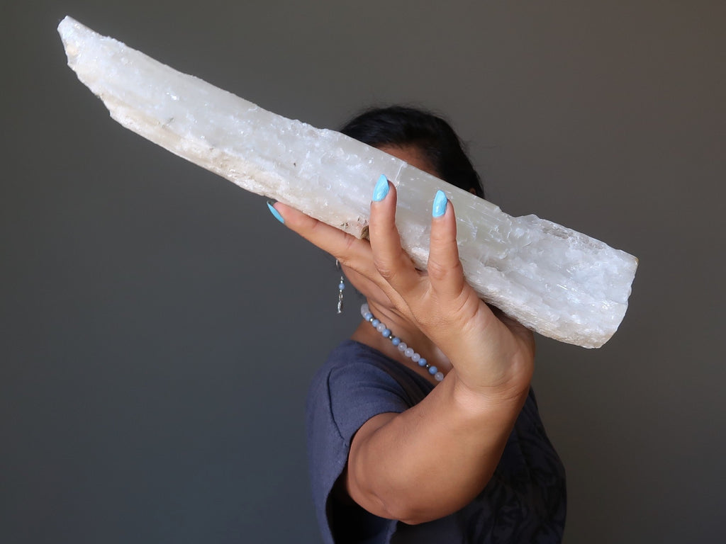 sheila of satin crystals holding up a large raw log of white selenite for the 4th dimension shift
