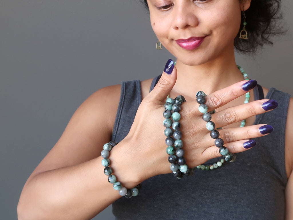 sheila of satin crystals with a hand full of raw emerald stretch bracelets