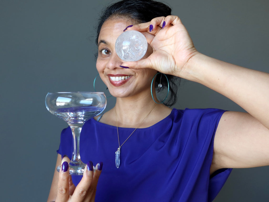 sheila of satin crystals holding up a martini glass and a clear quartz sphere