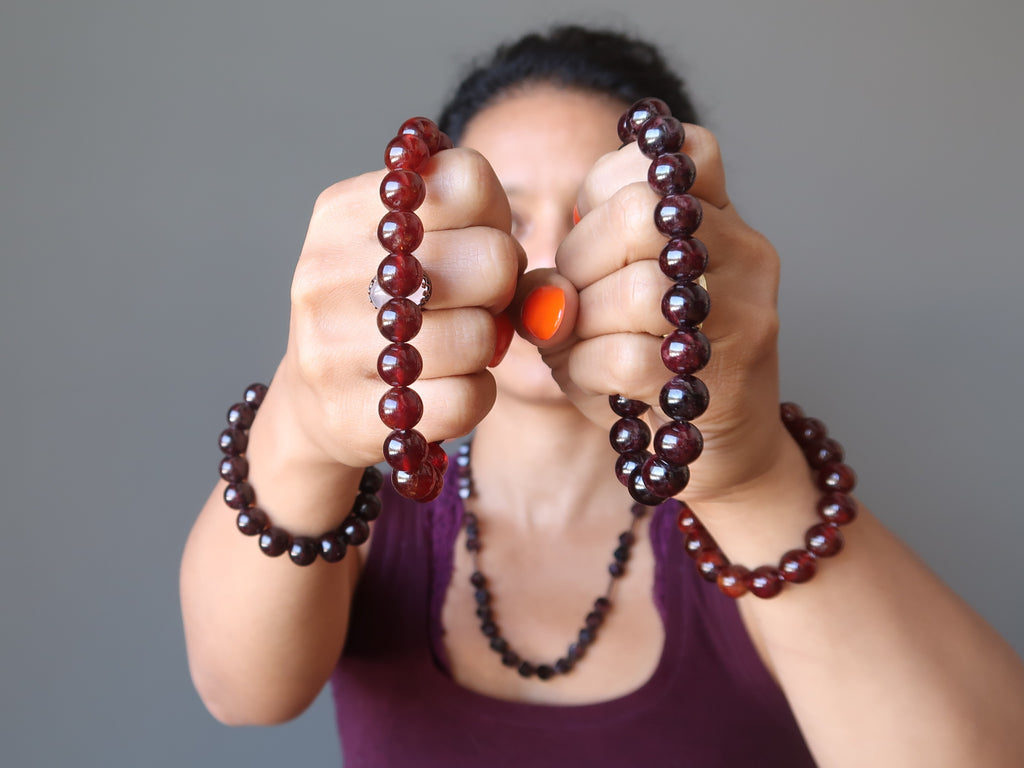 sheila of satin crystals holding red and hessonite garnet stretch bracelets