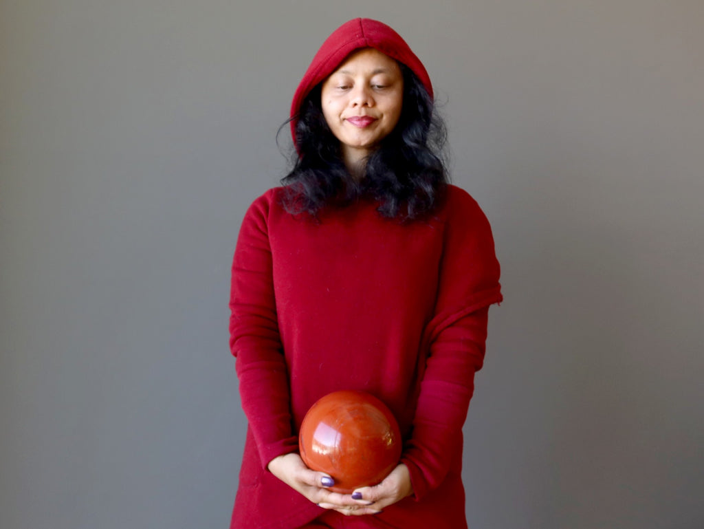 sheila of satin crystals wearing red holding a red jasper sphere at the root chakra