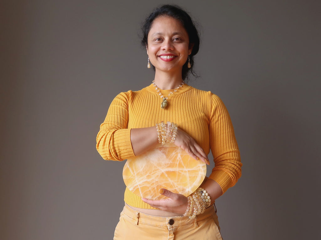 sheila of satin crystals holding a yellow calcite platter at her solar plexus chakra