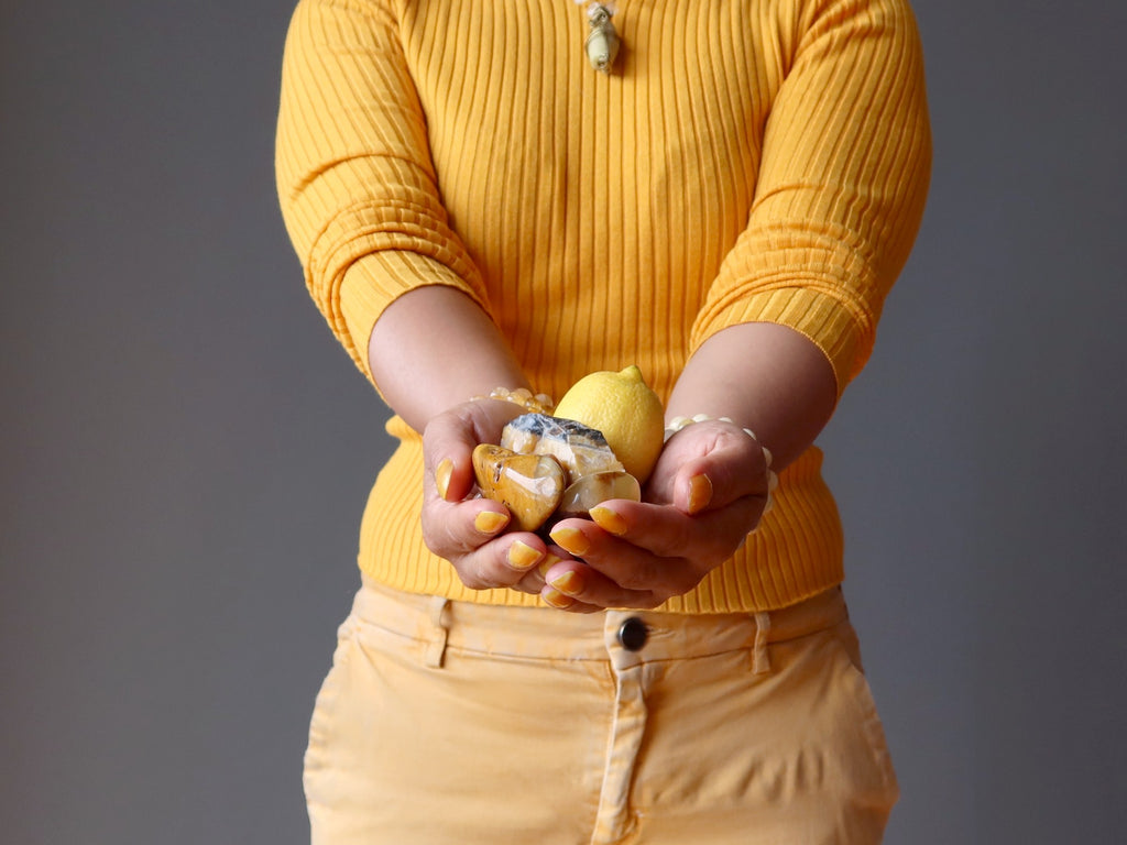 holding out yellow crystals and a lemon at the solar plexus chakra