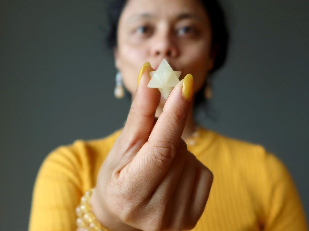 sheila of satin crystals holding a yellow calcite merkaba crystal in front of her mouth