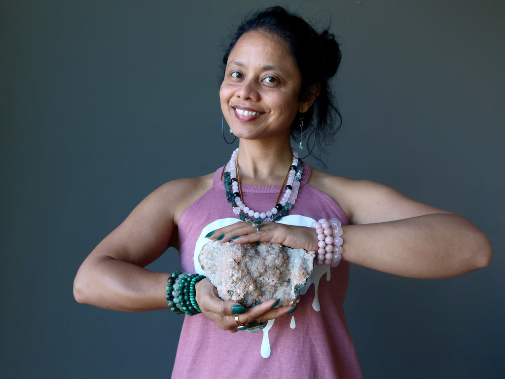 sheila of satin crystals wearing green and pink gemstone jewelry holding a stilbite cluster at her heart chakra