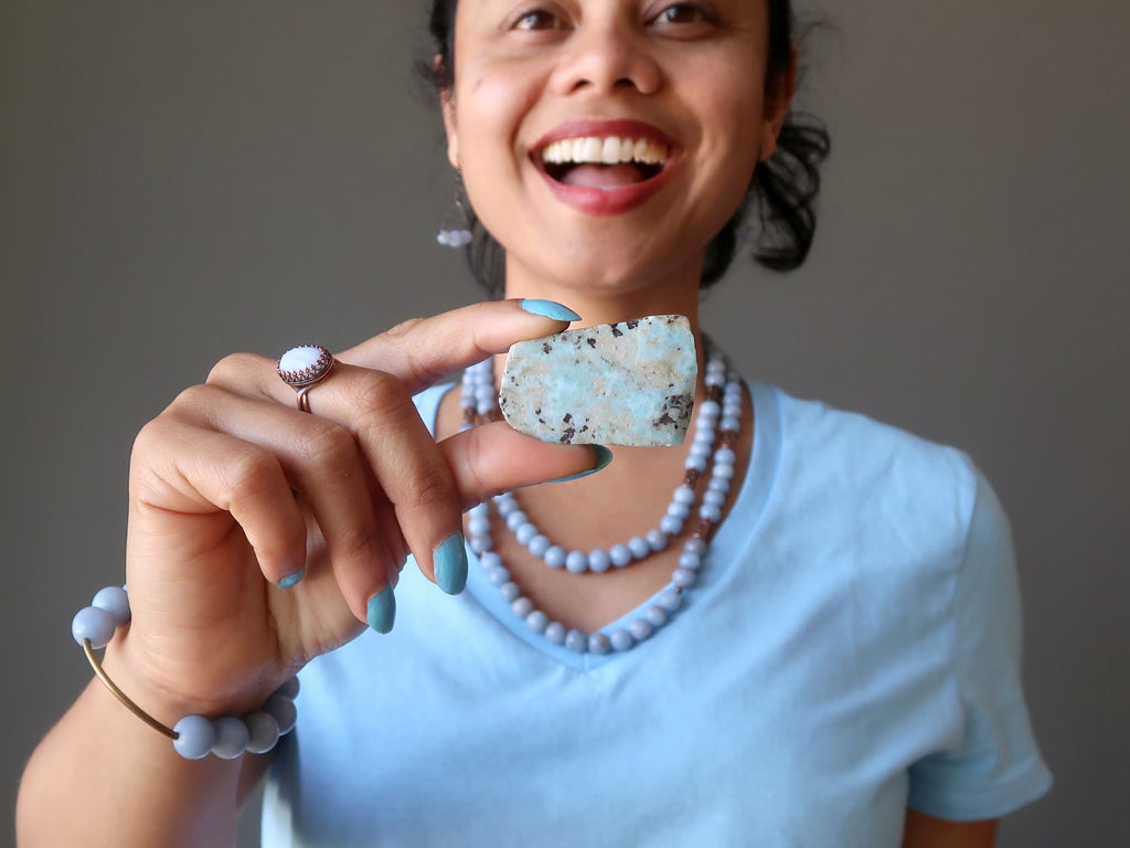 sheila of satin crystals holding larimar slab at her throat chakra