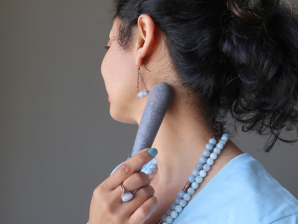 sheila of satin crystals massaging her throat chakra with blue aventurine wand