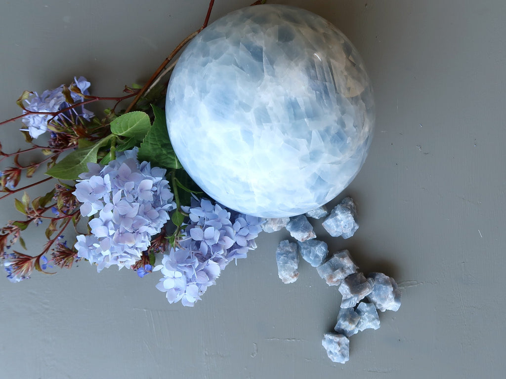 blue calcite ball, raw stones and blue flowers