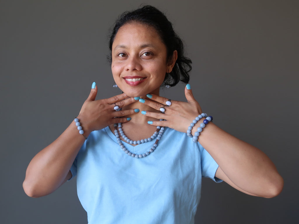 sheila of satin crystals in blue and blue jewelry touching her throat chakra