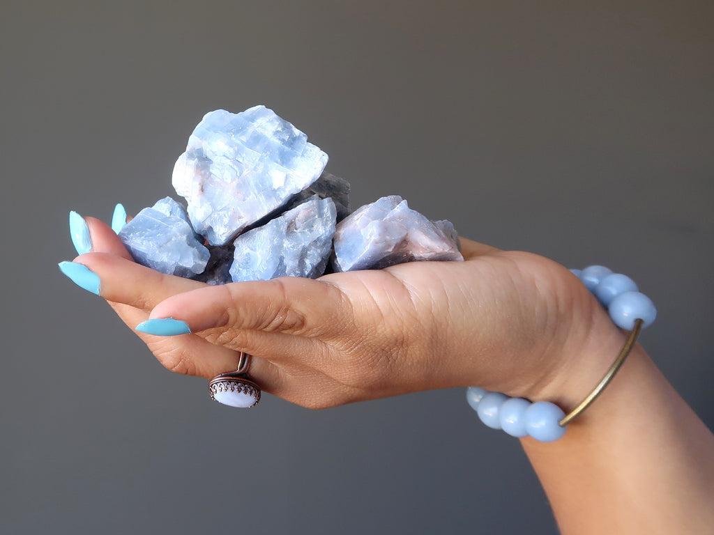 hand holding a pile of raw blue calcite stones
