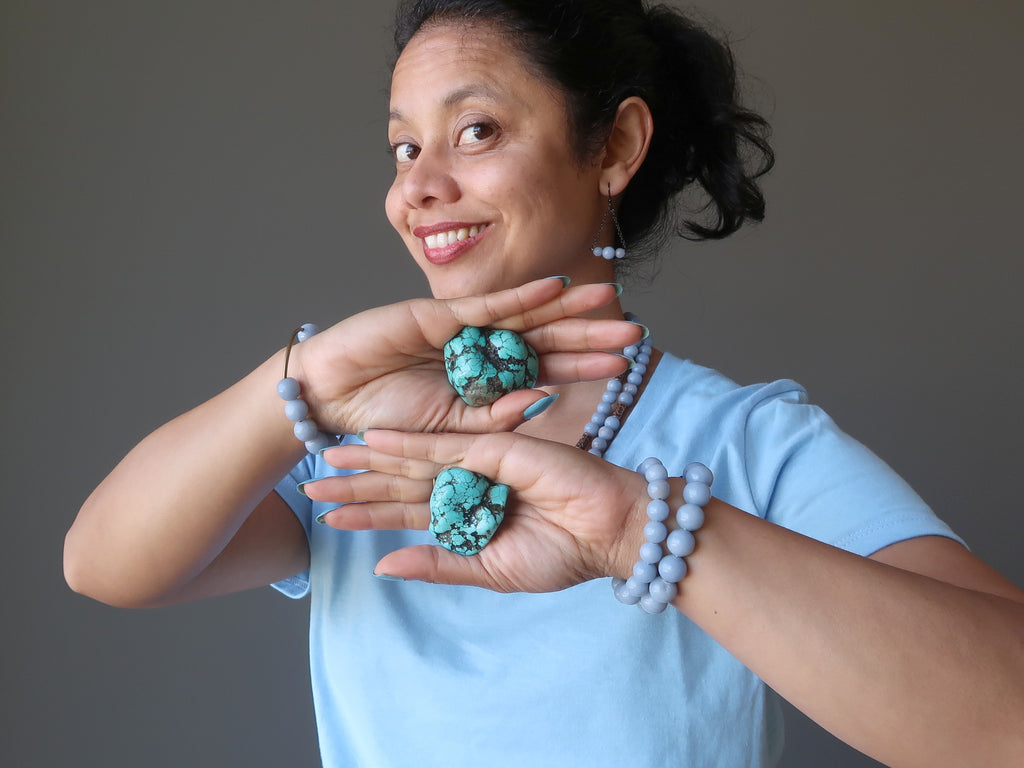 sheila of satin crystals holding turquoise stones at her throat chakra