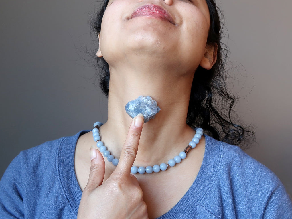 sheila of satin crystals with blue calcite stone on her throat to open the throat chakra
