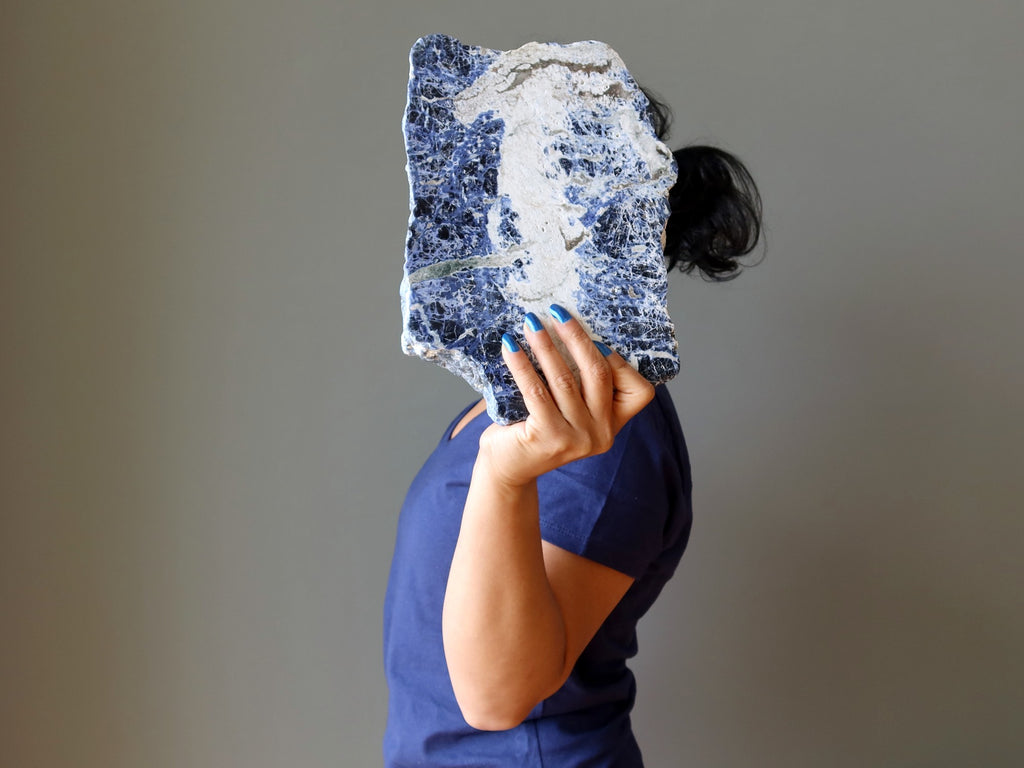 sheila of satin crystals holding up a sodalite slab