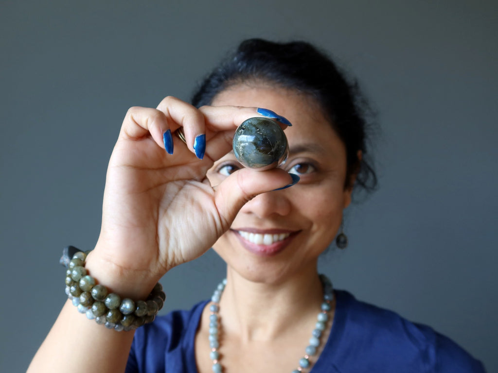 sheila of satin crystals with a labradorite wand pointed at her third eye chakra