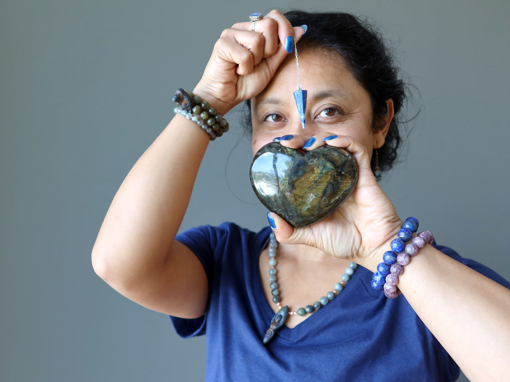 sheila of satin crystals holding a labradorite heart and lapis pendulum for the third eye chakra