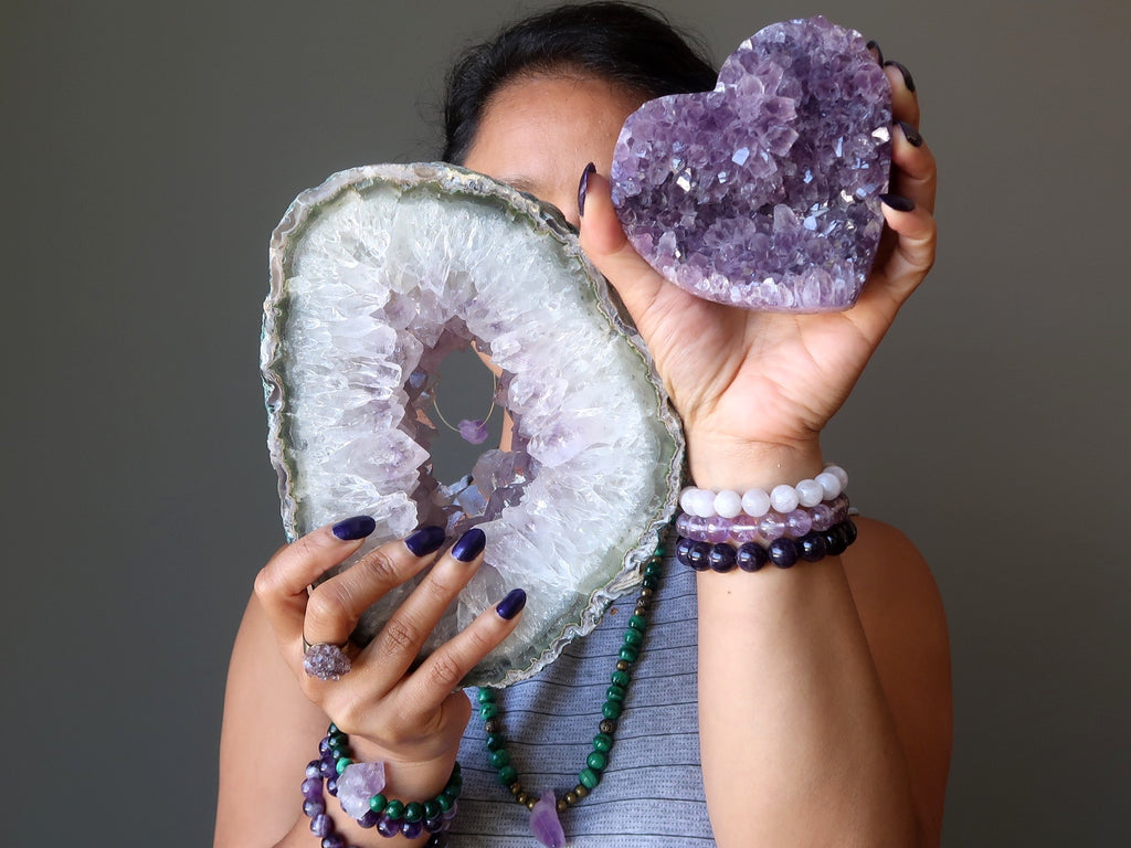 sheila of satin crystals holding up an amethyst geode and purple amethyst cluster heart for the crown chakra